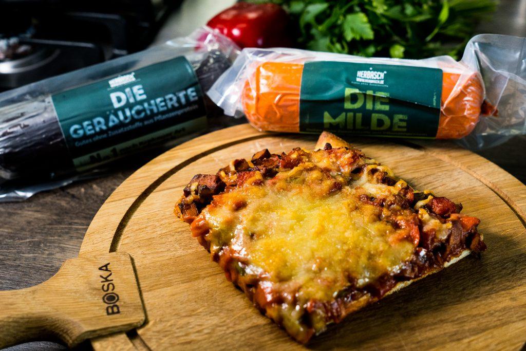Teufelskrusta oder auch Teufelspizza genannt. Vegane Fleischalternative, Gewürze und pflanzlicher Käse auf knusprigem Teig.